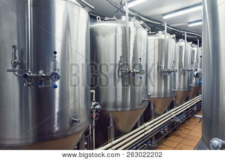 Lines Of Metal Tanks In Modern Brewery. Shopfloor With Brewery Facilities. Manufacturable Process Of