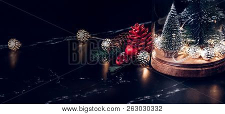 Christmas Tree And Glowing Light String And Pine Cone And Mistletoe Decoration On Marble Table And B