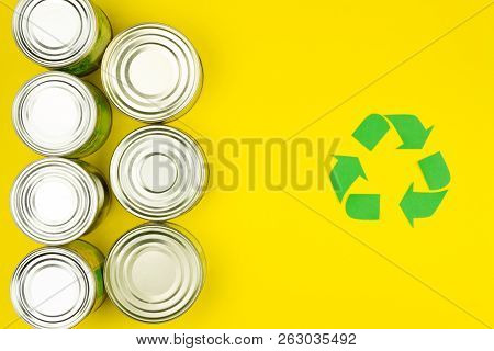 Green Recycle Reuse Sign Symbol With Metal Aluminium Cans On Yellow Background. Eco Ecology Environm