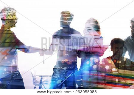 Silhouette Of Young Workers Shaking Hands In The Office. Concept Of Teamwork And Partnership. Double