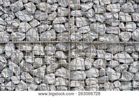 The Texture Of The Wall Of Small Gray Stones Under Iron Mesh. Natural Stone Wall Texture Photo, Ston