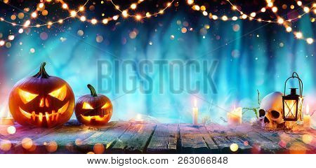 Halloween Party - Jack O Lanterns And String Lights On Table In Misty Forest