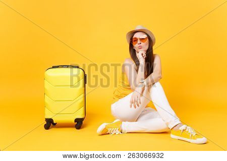 Traveler Tourist Woman In Summer Casual Clothes, Hat Sit With Suitcase Isolated On Yellow Orange Bac