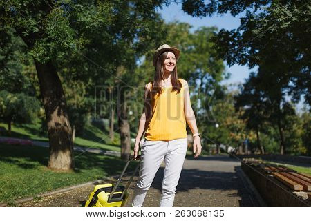Young Smiling Traveler Tourist Woman In Yellow Summer Casual Clothes, Hat With Suitcase Walking In C