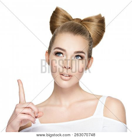 Pensive face of a young girl .  Young woman with a creative hairstyle got an idea. Girl pointing finger up isolated on on white background.