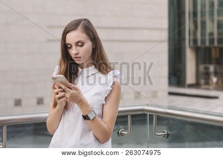 Young European Female In White Blouse Standing Outside And Holding A Mobile Phone In Her Hands And R