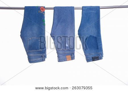 embroidered flowers jeans Jeans and two trousers on hangers