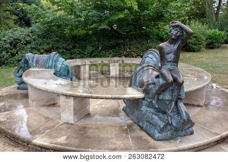 LEAMINGTON SPA, ENGLAND - August 10, 2018: An unusual bronze and marble seat sculpture with elephants and a boy in Jephson Gardens, Leamington Spa, England. By sculptor Nicholas Dimbleby in 1988.