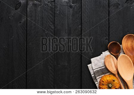 Wooden Spoons, Pumpkin And Dishtowel On Black Wooden Background With Copy Space. Top View Of Kitchen