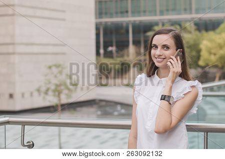 Happy And Successful Young Business Woman Talking Via Mobile Phone. European Female Calling Via Smar