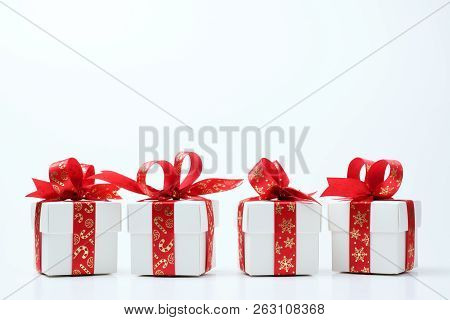 Four White Gift Boxes Tied With Christmas Theme Red Ribbon Isolated On White Background