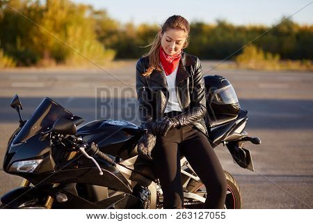 Outdoor Shot Of Pleased Female Bikes Puts On Leather Gloves, Dressed In Black Clothes, Poses On Moto