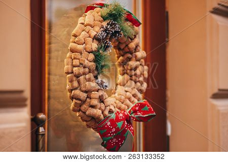 Creative Christmas Wreath Of Wine Corks, Pine Cones And Red Bows On Door Or Window  Of Wine Store In