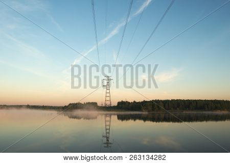 Power Line Crosses The River. The River Is Covered In Fog. The Blue Sky And The Power Line Are Refle