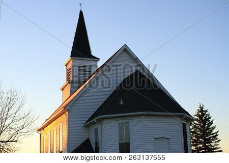 A Abandoned Church At Sunset Against A Blue Sky.