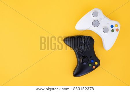 Black And White Joystick On A Yellow Background. White And Black Gamepad Is Isolated On A Yellow Bac