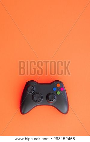 Black Joystick Is Isolated On A Red Background. Video Game Competition. Gaming Concept. Copyspace