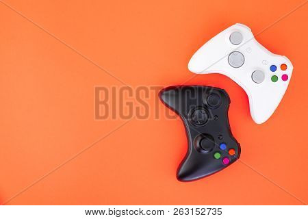 Black And White Joystick On A Red Background. White And Black Gamepad Is Isolated On A Red Backgroun