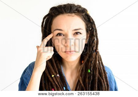 A Young Girl With Dreadlocks Shows A Gesture Using A Finger At Her Temple, Which Means Using Your Br