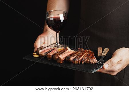 Man Holding Juicy Grilled Beef Steak With Spices And Red Wine Glass On A Stone Cutting Board On A Bl