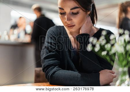 Young Beautiful Woman Looking At Menu Deciding What To Order In Modern Cafe.