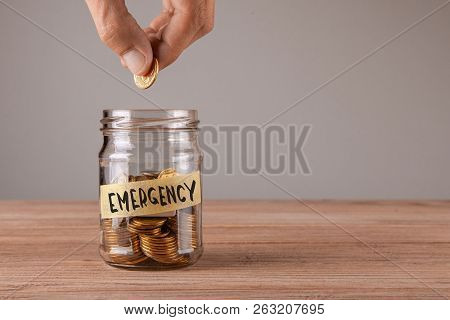 Emergency. Glass Jar With Coins And An Inscription Emergency. Man Holds  Coin In His Hand.