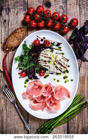 Appetizing Dish Of Meat And Cheese With Greens On A Wooden Background A
