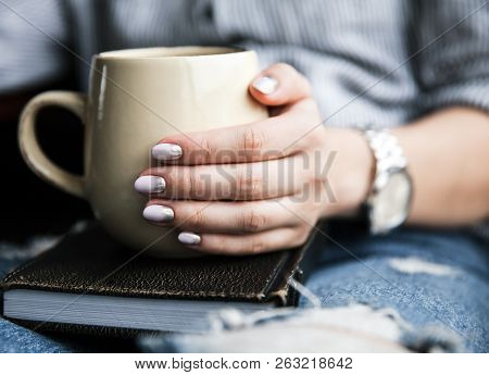 A Young Girl With A Beautiful Manicure Holds A Book With A Cup Of Coffee. Fashion Style A