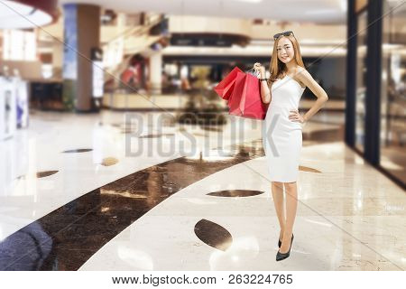 Attractive Chinese Woman Carrying Red Paper Bags At Mall. Black Friday Concept
