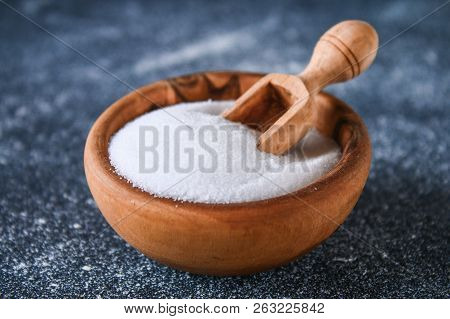 Crystals Of Shallow Salt In A Wooden Bowl On A Dark Gray Table. Background For Advertising Salt. Tab