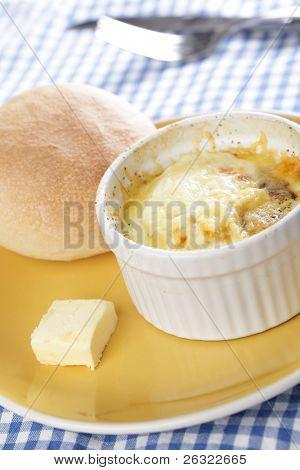 Breakfast with Swiss styled baked eggs in ramekin with the bun