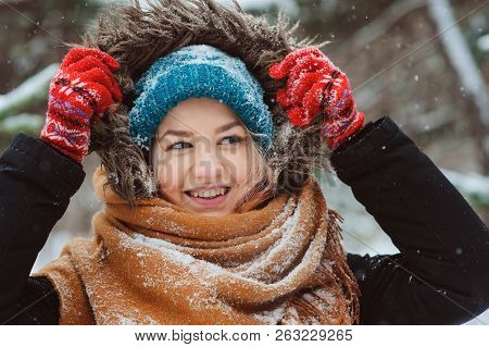 Winter Portrait Of Happy Young Woman Walking In Snowy Forest In Warm Outfit, Red Knitted Gloves And