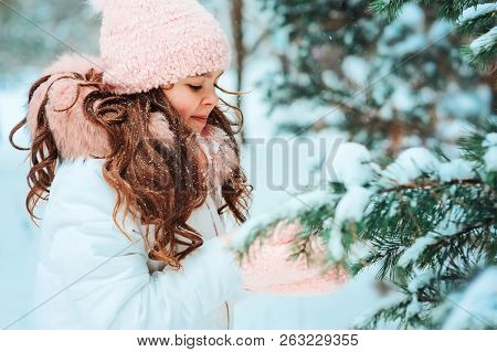 Winter Portrait Of Happy Kid Girl In White Coat And Hat And Pink Mittens Playing Outdoor In Snowy Wi