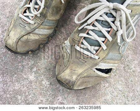 Old And Worn Out Trainers With A Hole