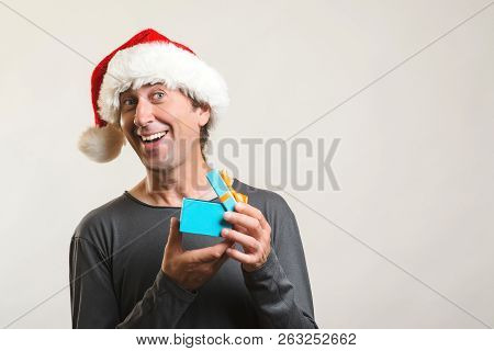 Emotionally Happy Guy Open Christmas Gift. Man In Santa Hat With Gift On White Background. Copy Spac