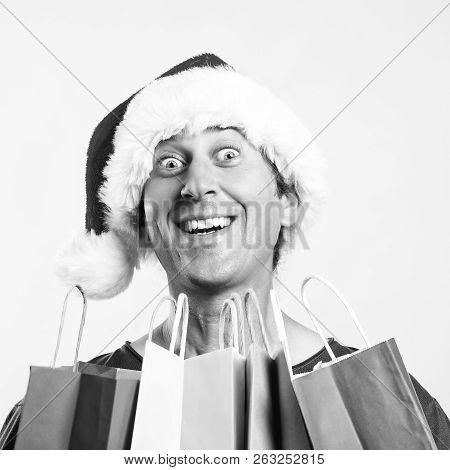 Christmas Man. Man Holding Shopping Bags. Christmas Sales. Man Wearing Santa Claus Hat In Shopping T