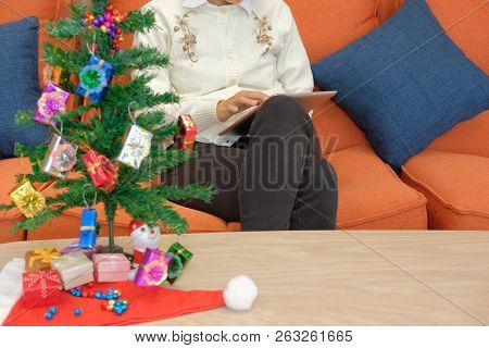 Woman Sitting On Sofa Using Tablet At Home. Girl Texting Message On Touchpad During Xmas. Christmas