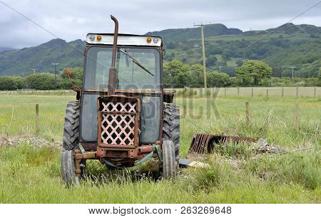 Rusting Old Vintage Tractor And Farm Machinery In The Uk Countryside. Symbol Of Rural And Agricultur