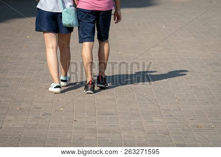On A Sunny Day, A Couple Of People Walk Along The Sidewalk. The Human Shadows Are Visible On The Sid