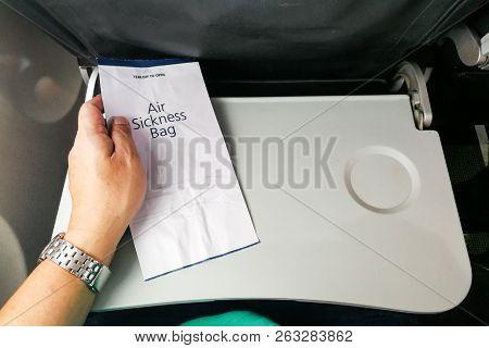 Passenger Holding Air Sickness Vomit Bag In Airplane