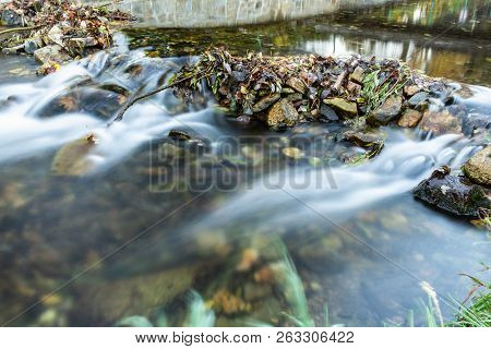Mountain Creek With Clear Water Gently Cascading Down Through Moss Covered Rocks In Soft Light