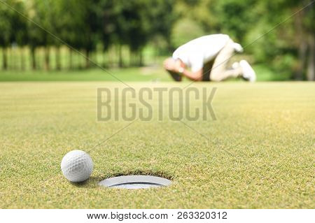 Man Golfer Feeling Disappointed After A Putted Golf Ball Missed The Hole
