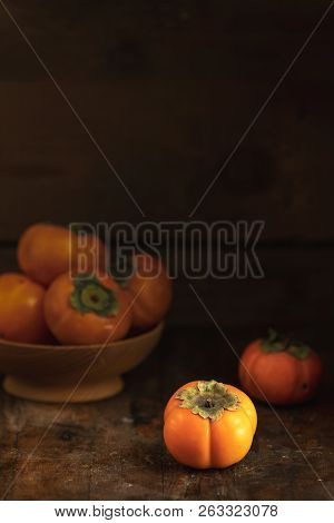 Autumn Harvest Persimmon Fruits In Bowl On A Wooden Table Background. Copy Space. Dark Rustic Style.