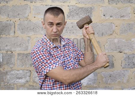 Angry Man With Sledgehammer On The Brick Wall Background. Working Concept