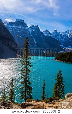 Province of Alberta, Canadian Rockies. The cold northern sun is reflected in the icy water of the lake Moraine. The concept of ecological, photographic and active tourism