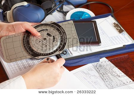 Pilot equipment with airplane pilot hand filling in flight plan, other tools like flight computer used for aviation calculations, protractor, kneepad with charts and professional headset poster
