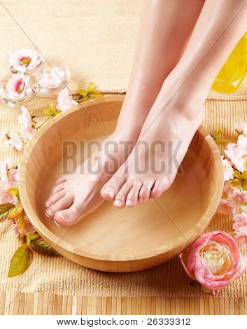 Close-up of beautiful female feet in wooden bowl filled with fluid cosmetics, flowers all around. Concept of natural spa treatment.