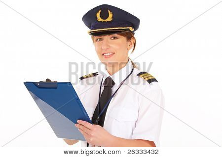 Beautiful woman pilot wearing uniform with epauletes and hat with golden wings, writting on notepad, standing isolated on white background.