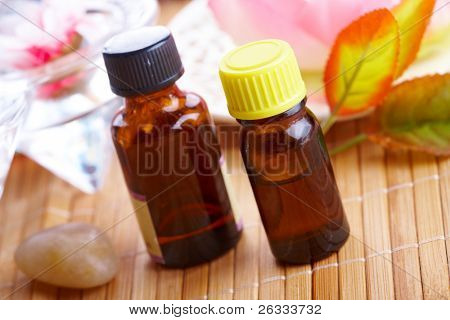 Bottles of aromatic oil with flowers in a background. Traditional alternative therapy or medicine, concept of healthy lifestyle, aromatherapy.