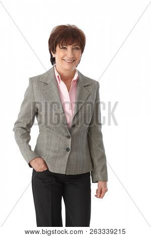 Senior businesswoman standing in trousers and jacket, smiling with hand in pocket.